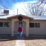 Miss Giron in front of her repaired home